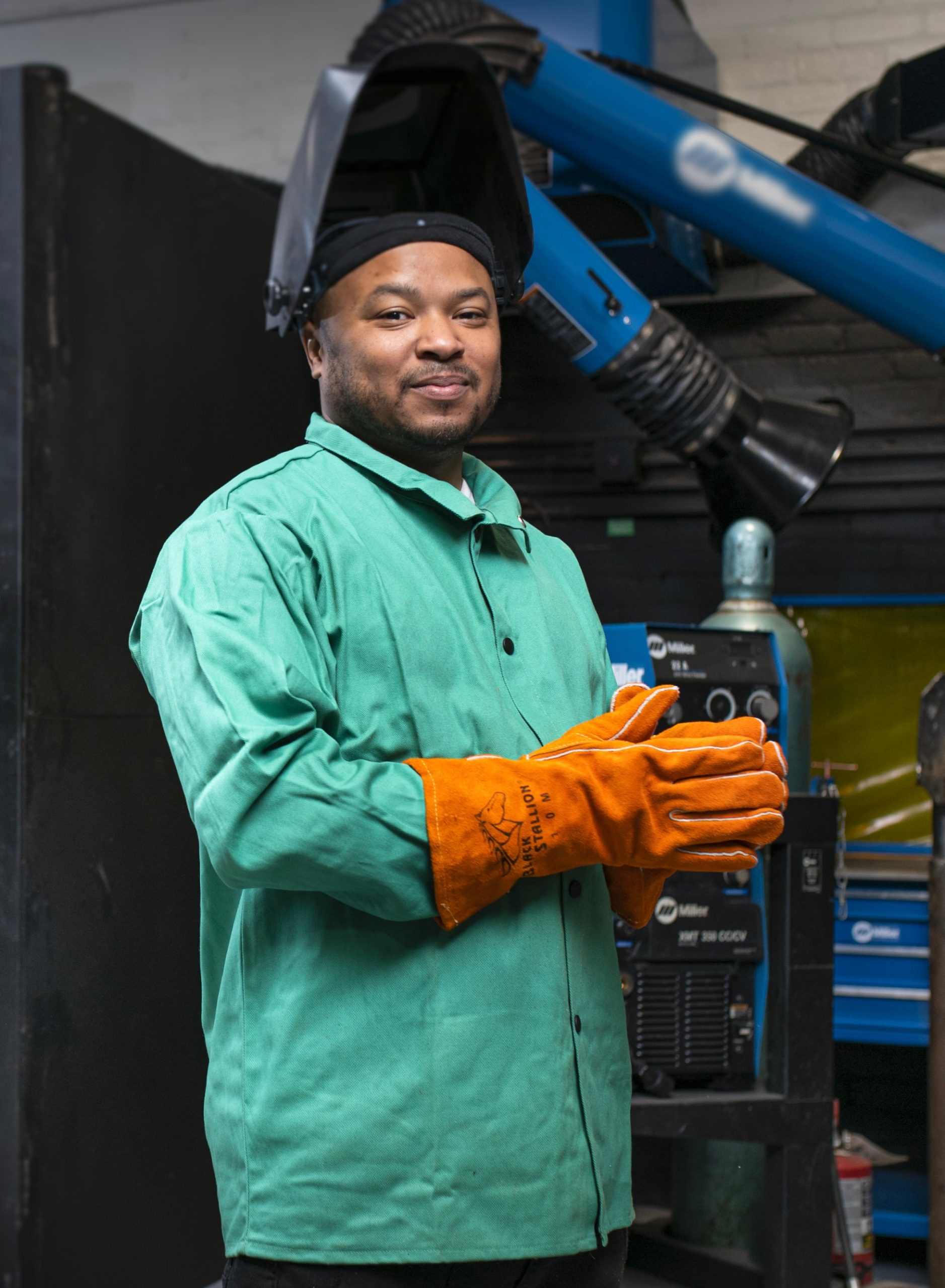 A young black man wearing a welder's mask and a green workman's suit, smiling