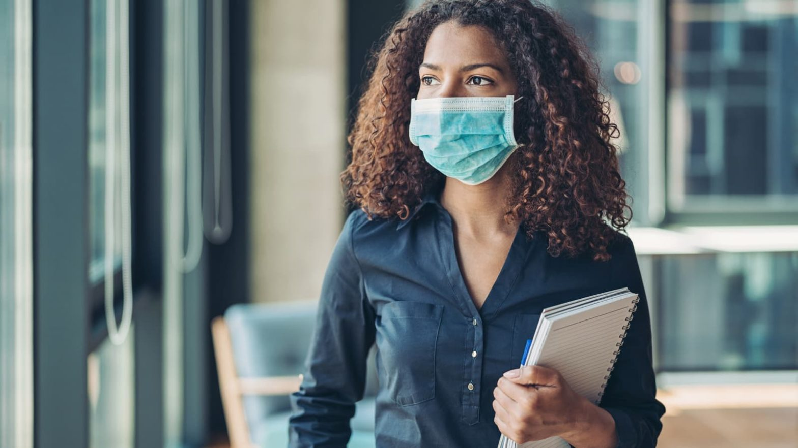 Photo of a multiracial woman wearing a blue medical face mask and carrying a notebook in an office setting