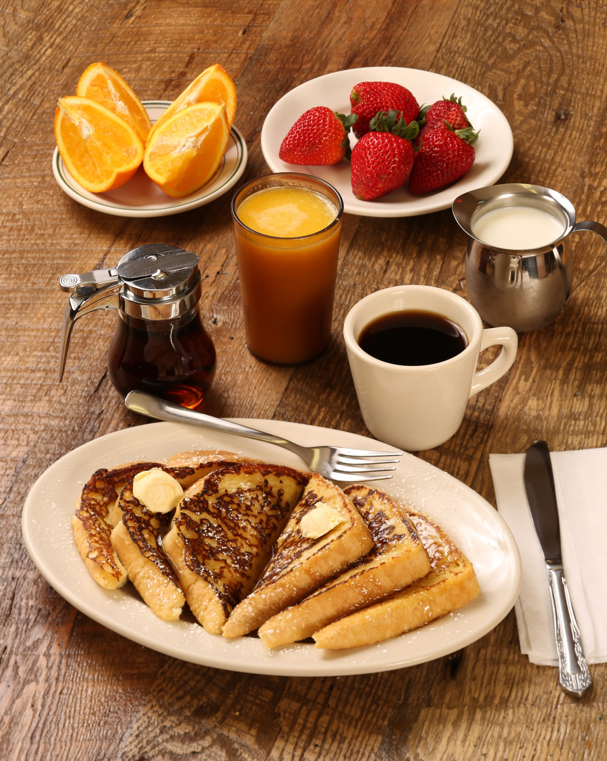 A diner breakfast of french toast, coffee, orange juice, orange slices, strawberrys, and maple syrup