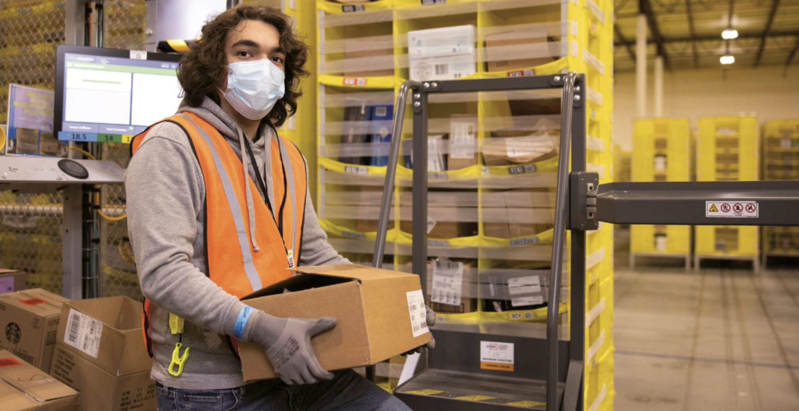 A person carrying a box in Amazon warehouse