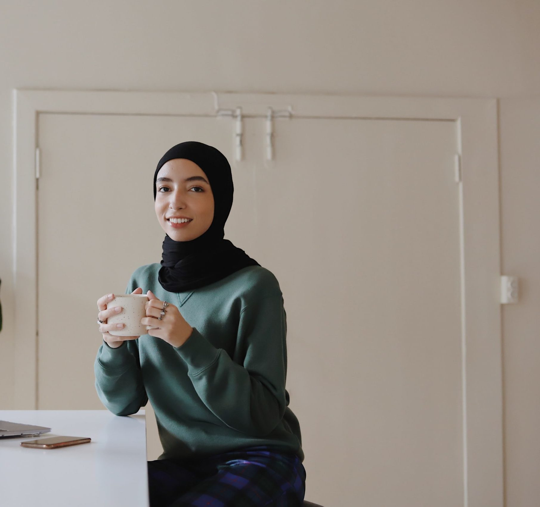 A young woman in a green sweater and a black hijab holding a mug and smiling