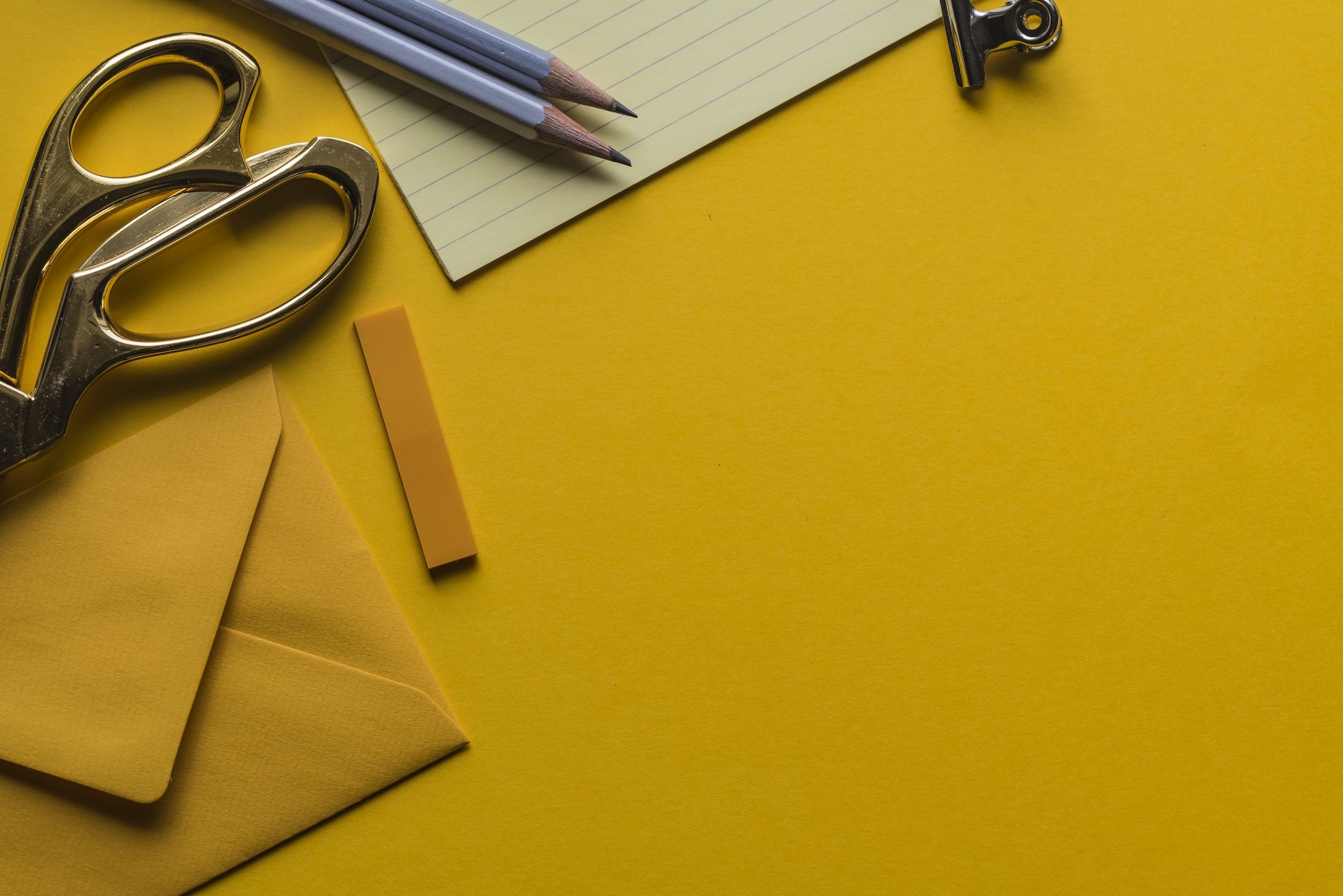 A yellow background with envelopes, notepads, folder tabs, pencils, and scissors set on top