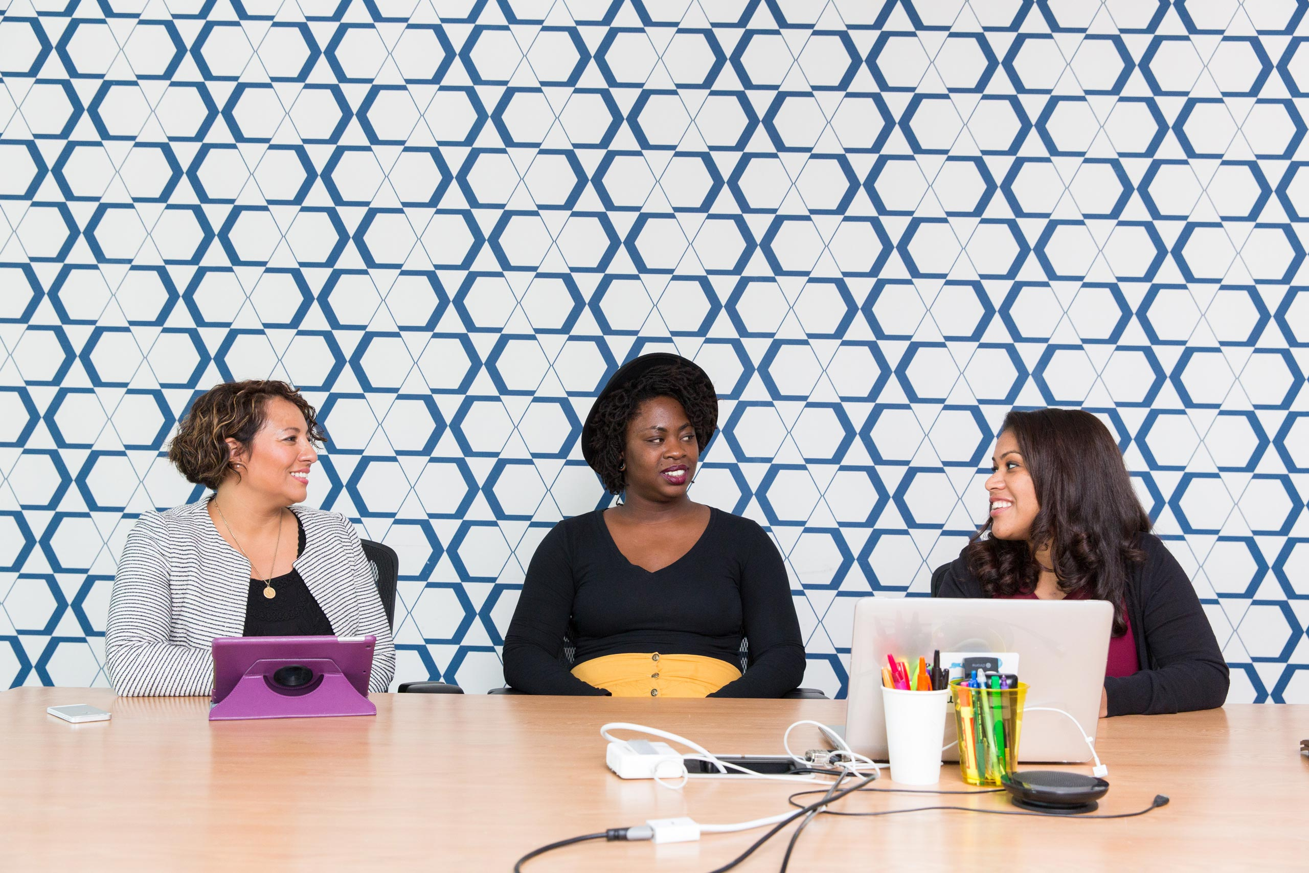 3 women consulting with each other professionally with laptops and ipads on the table in front of a blue patterned tile background