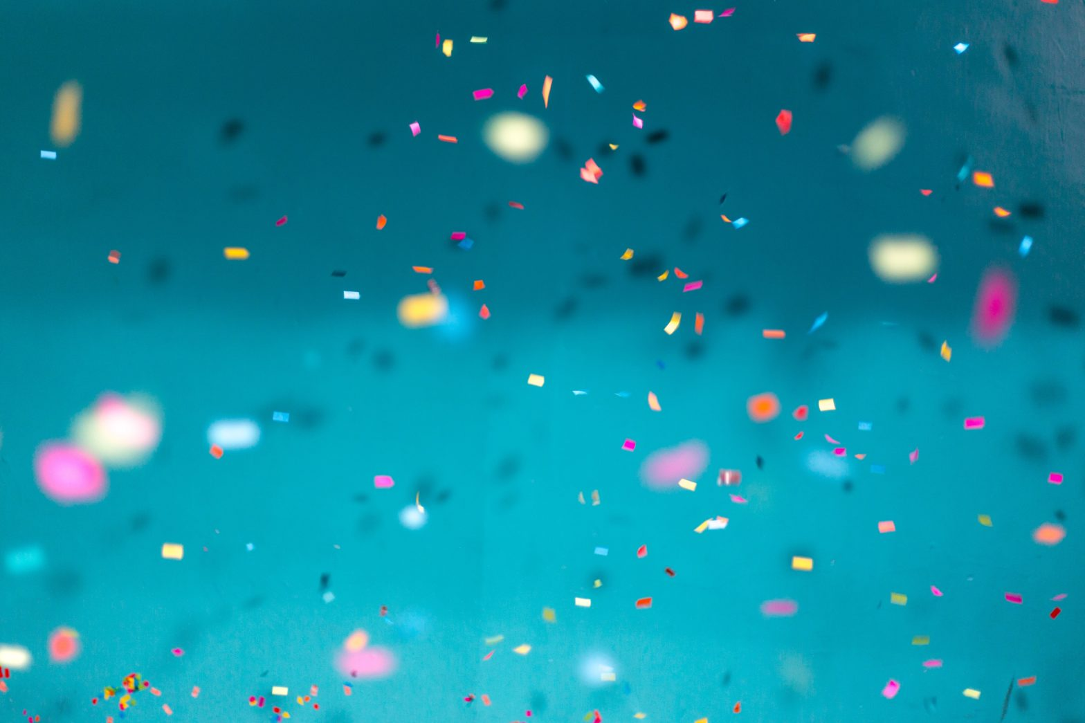 A blue background with multicoloured confetti falling in front of it