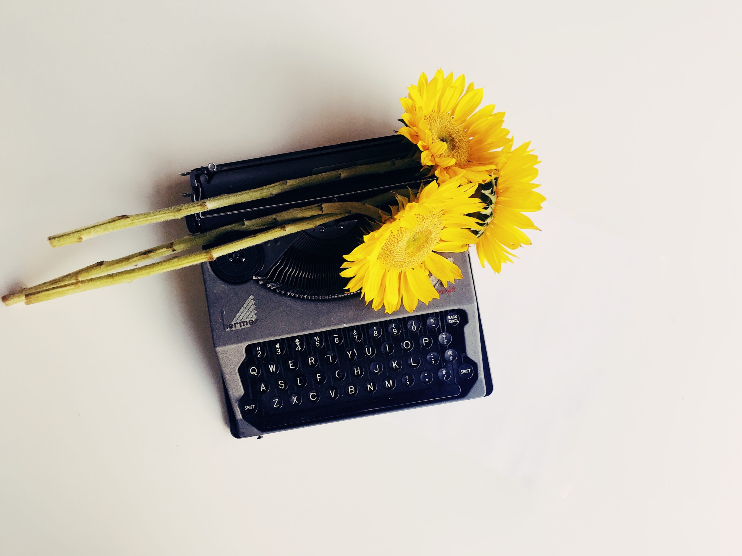 A black typewriter with yellow sunflowers set on top of it, all on a plain taupe background